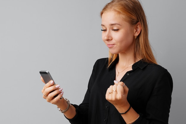 Happy young casual woman looking at her phone over gray
