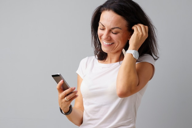 Happy young casual woman looking at her phone