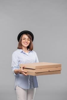 Счастливая молодая повседневная женщина со стопкой картонных пакетов, доставляющая вам пиццу или другой заказ еды