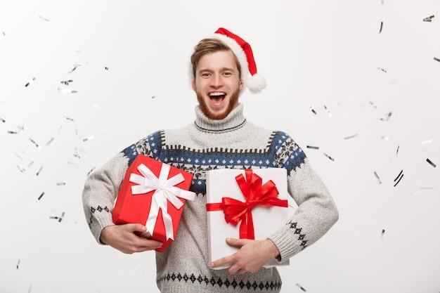 색종이와 선물 상자를 들고 행복 한 젊은 백인 수염 남자