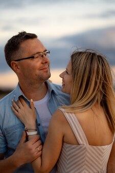 夏のビーチで日没の幸せな若い白人の美しいカップル背景の美しい空