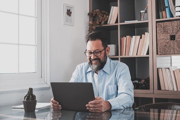 Счастливый молодой кавказский бизнесмен улыбается, работая онлайн, смотря подкаст веб-семинара на ноутбуке и изучая образовательный курс, конференц-связь, делать заметки, сидеть за рабочим столом, концепция электронного обучения