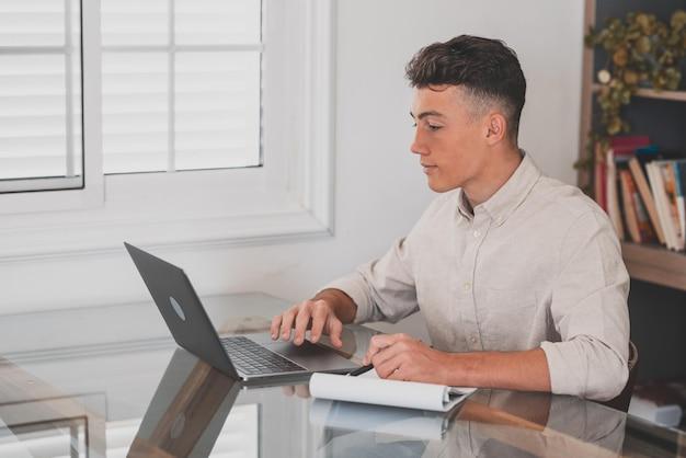 Счастливый молодой кавказский бизнесмен улыбается, работая онлайн, наблюдая за подкастом веб-семинара на ноутбуке и изучая образовательный курс, конференц-связь, делая заметки, сидеть за рабочим столом, концепция электронного обучения