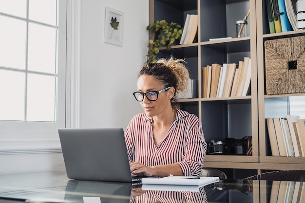 Happy young caucasian businesswoman smiling working online watching webinar podcast on laptop and learning education course conference calling make notes sit at work desk, elearning concept