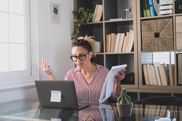 Счастливая молодая кавказская бизнесвумен, улыбаясь, работает онлайн, смотрит подкаст вебинара на ноутбуке и изучает образовательный курс, конференц-связь, делает заметки, сидя за рабочим столом, концепция электронного обучения