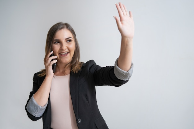 Happy young caucasian businesswoman with phone waving hand