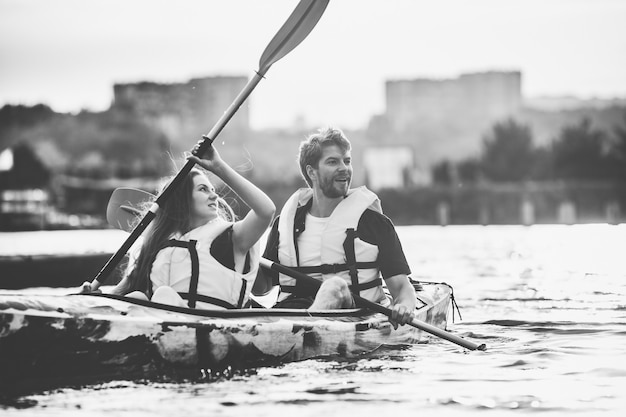 Happy young caucasian couple kayaking on river with sunset in the backgrounds. having fun in leisure activity. happy male and female model laughting on the kayak. sport, relations concept. colorless.