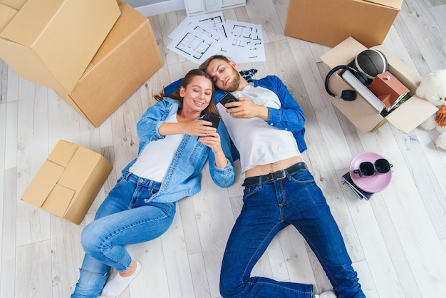 Happy young caucasian couple lying down on the wooden floor and messaging at phonesduring having break while moving to new house.