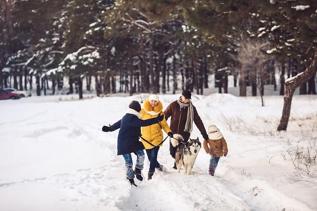 Счастливая молодая кавказская семья весело бегает с собакой зимой в сосновом лесу