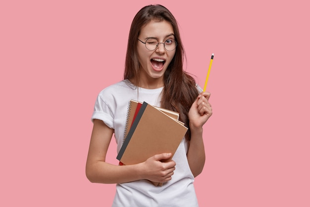 Happy young caucasian female genius gets good idea, blinks eye, holds pencil, carries notebooks, has fun indoor