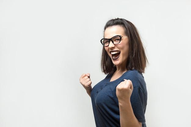 眼鏡をかけた青いシャツを着た幸せな若い白人女性は、くいしばられた握りこぶしを喜びのために持ち上げます