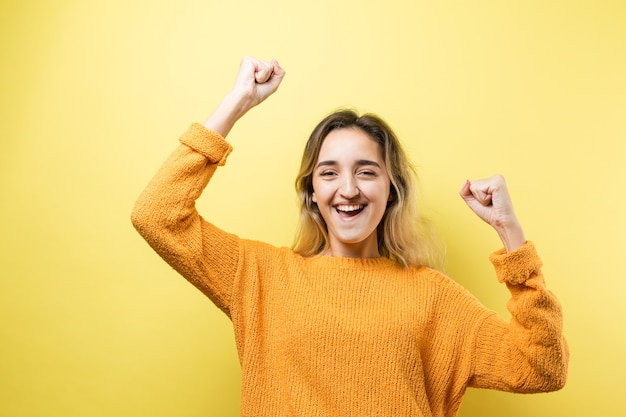 Happy young caucasian femalein an orange sweater lifts a clenched fist up for joy