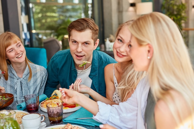 Счастливые молодые кавказские друзья собираются в кафе
