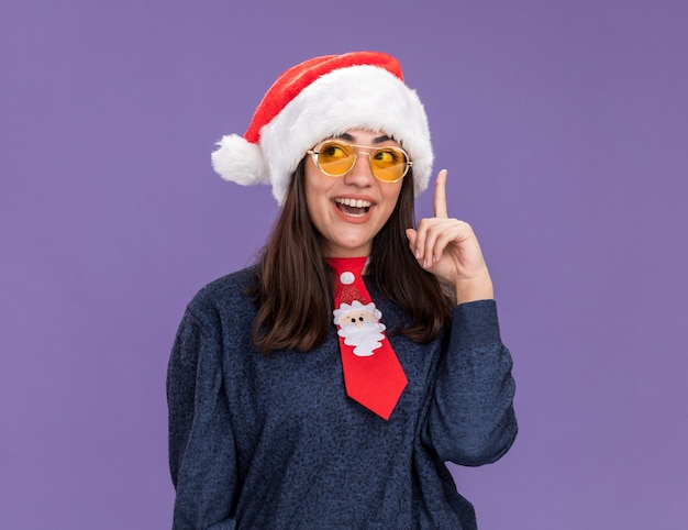 Happy young caucasian girl in sun glasses with santa hat and santa tie points up looking at side isolated on purple wall with copy space