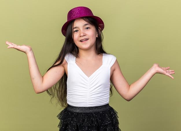 Felice giovane ragazza caucasica con cappello da festa viola che tiene le mani aperte isolate sulla parete verde oliva con spazio di copia