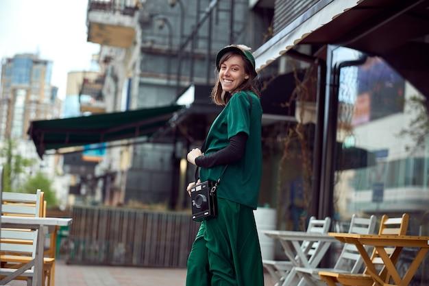 녹색 드레스에 행복 한 젊은 백인 아가씨는 아늑한 카페 근처를 걷고있다