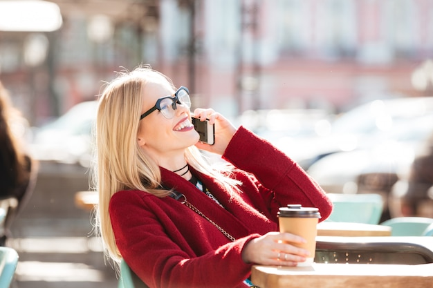 Happy young caucasian lady talking by phone drinking coffee.