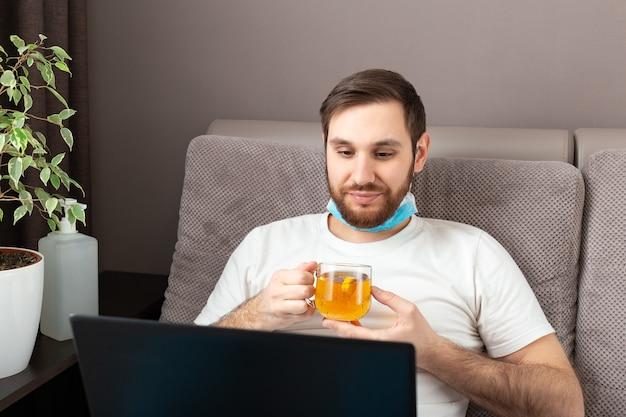 Счастливый молодой кавказский человек в медицинской маске пьет чай во время работы из дома, используя ноутбук.