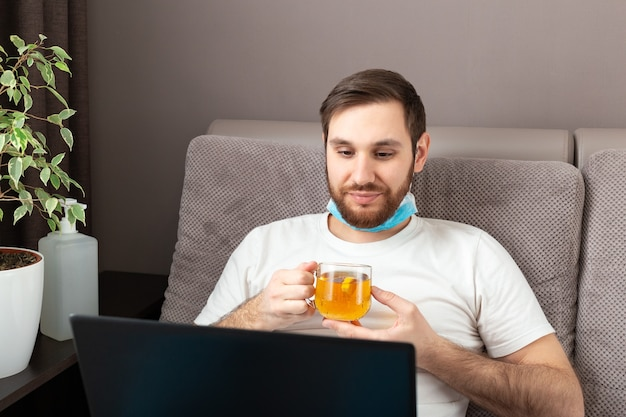 Happy young caucasian man in medical face mask drink tea while working from home using laptop.