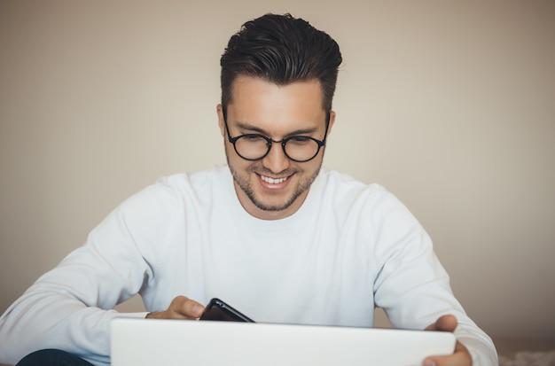 안경과 함께 행복 한 젊은 백인 남자는 노트북과 모바일을 사용하여 폐쇄하는 동안 온라인으로 뭔가를 구입합니다