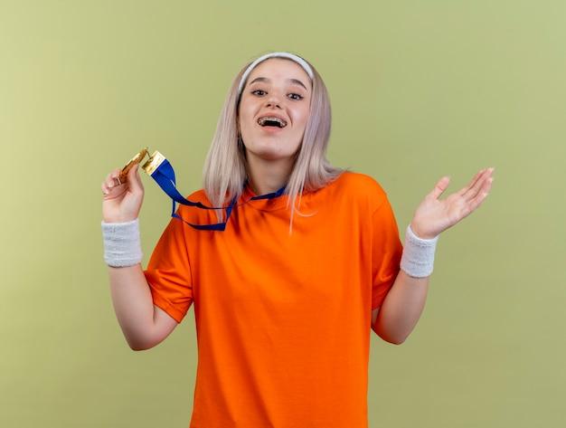 Felice giovane ragazza sportiva caucasica con bretelle che indossa fascia e braccialetti tiene la medaglia d'oro