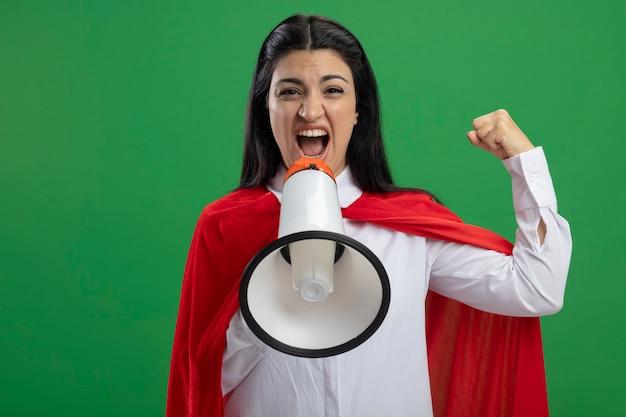 幸せな若い白人のスーパーヒーローの女の子がスピーカーで叫んで、コピースペースで緑の壁に分離された拳を1つ立てる