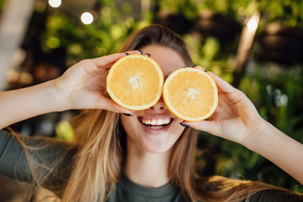 Happy young caucasian woman holding fresh oranges in front of eyes and smiling