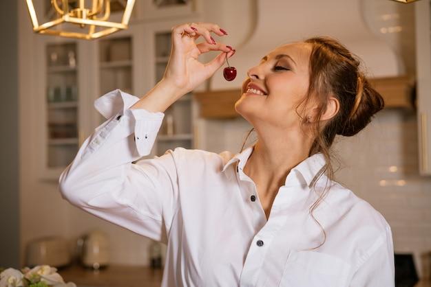 부엌 건강 비타민 식품 개념에 달콤한 체리를 먹고 흰 셔츠에 행복 한 젊은 백인 여자