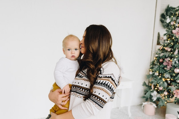 Happy young caucasian woman kissing her baby
