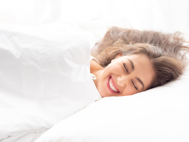 Happy young caucasian woman sleeping in bed with tranquil mind