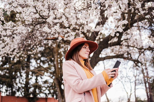 Happy young caucasian woman using mobile phone at sunset over almond tree blossoming. springtime and technology concept