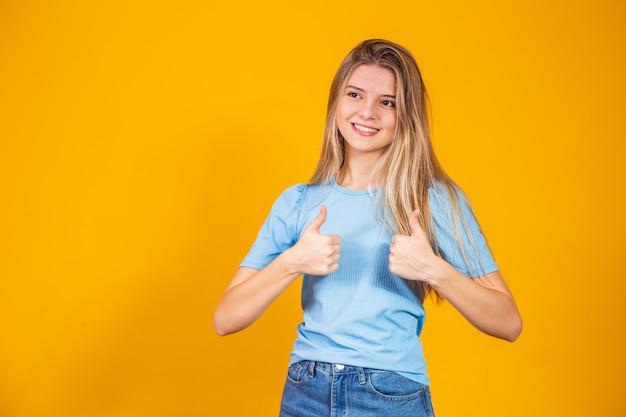 파란색 셔츠를 입은 행복한 젊은 백인 여성이 엄지손가락을 치켜들고 누군가에게 지지와 존경을 표하며 행복하게 웃고 있습니다. 신체 언어. 나는 그것을 좋아. 잘 했어요. 잘 했어요.