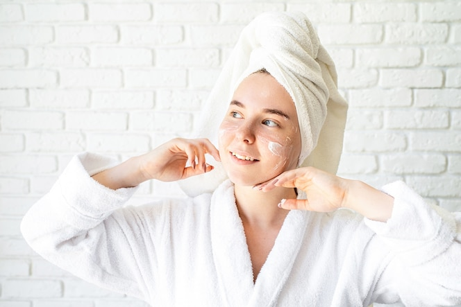 Happy young caucasian woman in white bath towel applying face cream at home