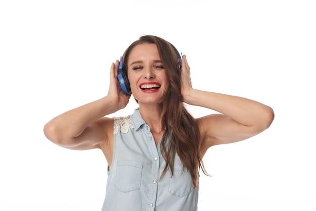エネルギッシュな音楽、孤立した背景を聴きながら青いヘッドフォンを保持している目を閉じて幸せな若い白人女性