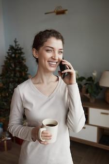 Счастливая молодая кавказская женщина с кружкой звонит родственникам по телефону, желая им счастливого рождества