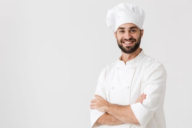 유니폼을 입고 포즈를 취하는 행복 한 젊은 요리사.