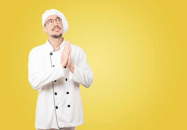 Happy young chef praying gesture