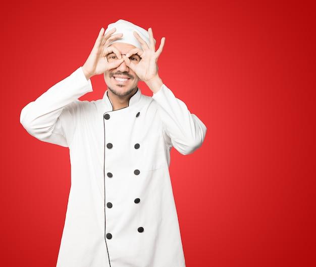 Счастливый молодой шеф-повар, использующий его руки как бинокль