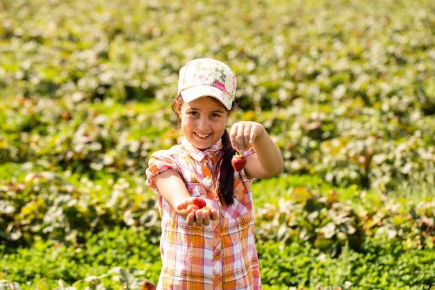 Счастливый маленький ребенок девочка собирает и ест клубнику на плантации