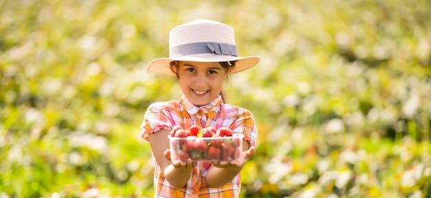 Счастливая маленькая девочка собирает и ест клубнику на плантации