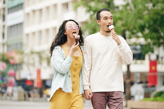 Happy young chinese boyfriend and girlfriend holding hands, walking on city street and eating delicious icecream