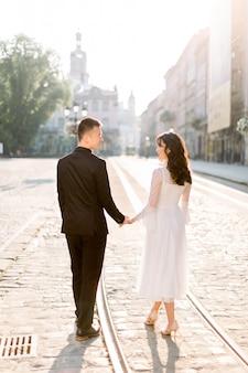 Счастливые молодые китайские пары гуляя на улицы старого центра города, стоя на tramline.