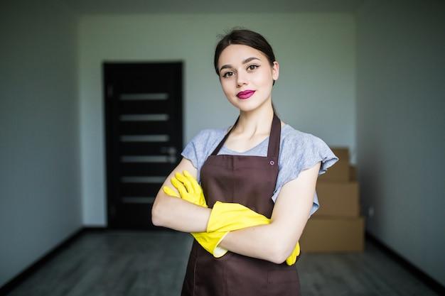 ゴム手袋をはめて、春の大掃除の準備をしている幸せな若い掃除婦