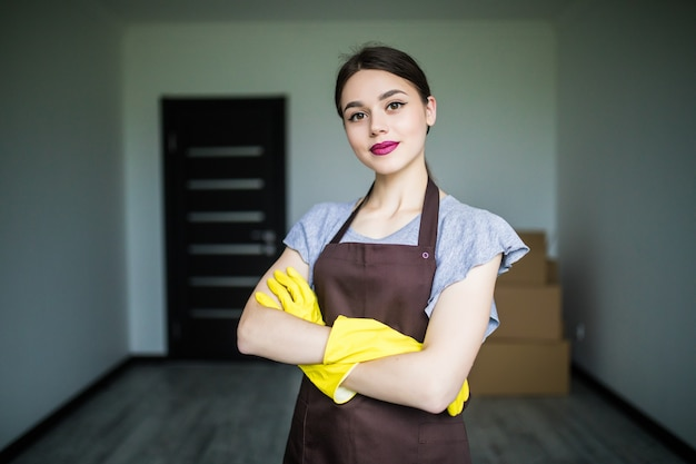 Happy young cleaning lady putting on rubber gloves, getting ready for spring cleaning