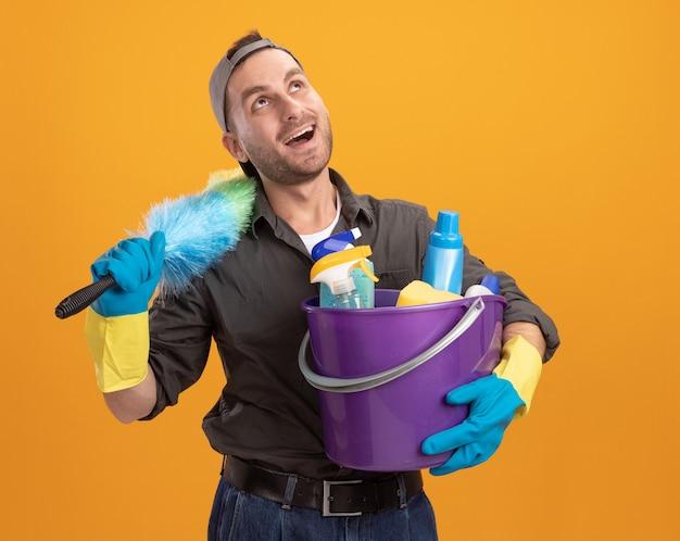 Felice giovane uomo delle pulizie che indossa abiti casual e berretto in guanti di gomma che tiene secchio con strumenti di pulizia e spolverino colorato guardando con il sorriso sul viso in piedi sopra la parete arancione