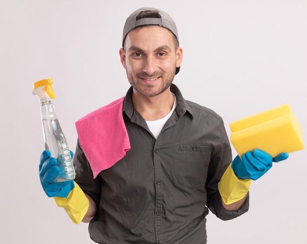 Felice giovane uomo delle pulizie che indossa abiti casual e berretto in guanti di gomma tenendo spray per la pulizia e spugna con uno straccio sulla sua spalla sorridendo allegramente in piedi sopra la parete arancione
