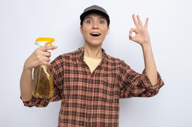 Felice giovane donna delle pulizie in abiti casual e berretto che tiene in mano uno spray per la pulizia che sorride allegramente mostrando il segno ok in piedi sul bianco
