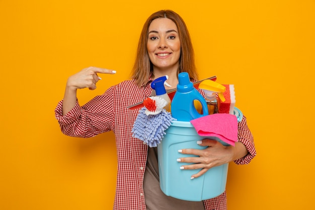 Happy young cleaning woman in plaid shirt holding bucket with cleaning tools looking at camera smiling cheerfully pointing with index finger at herself standing over orange background