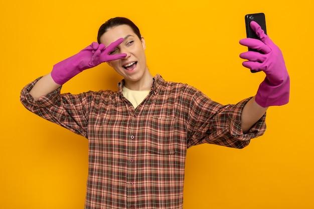 Felice giovane donna delle pulizie in camicia a quadri in guanti di gomma che tiene smartphone facendo selfie sorridente mostrando il segno a v sopra gli occhi in piedi sul muro arancione