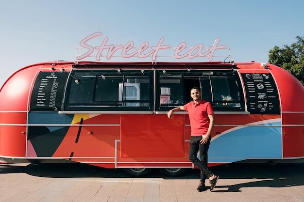 Счастливый молодой клерк в униформе, стоящий у уличного фургона с едой